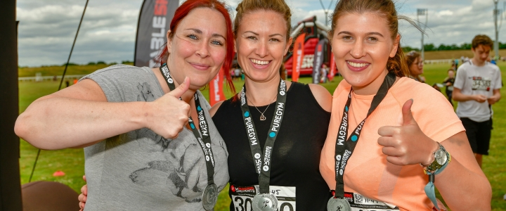 Palmers Solicitors trio raise hundreds for charity at inflatable 5k run